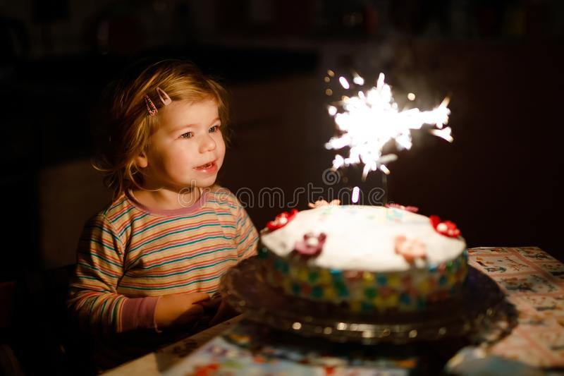 Adorable little toddler girl celebrating second birthday. Baby child eating marshmellows decoration on homemade cake. Indoor. Happy healthy toddler is suprised royalty free stock images