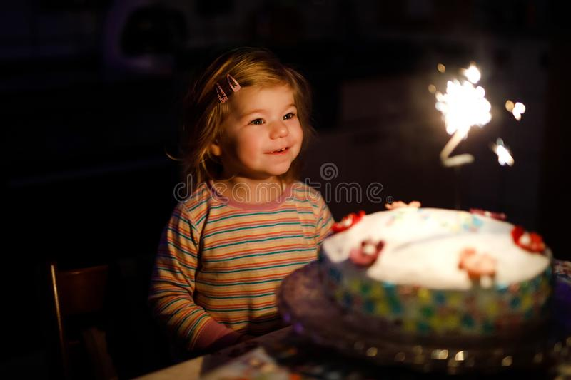 Adorable little toddler girl celebrating second birthday. Baby child eating marshmellows decoration on homemade cake. Indoor. Happy healthy toddler is suprised royalty free stock image