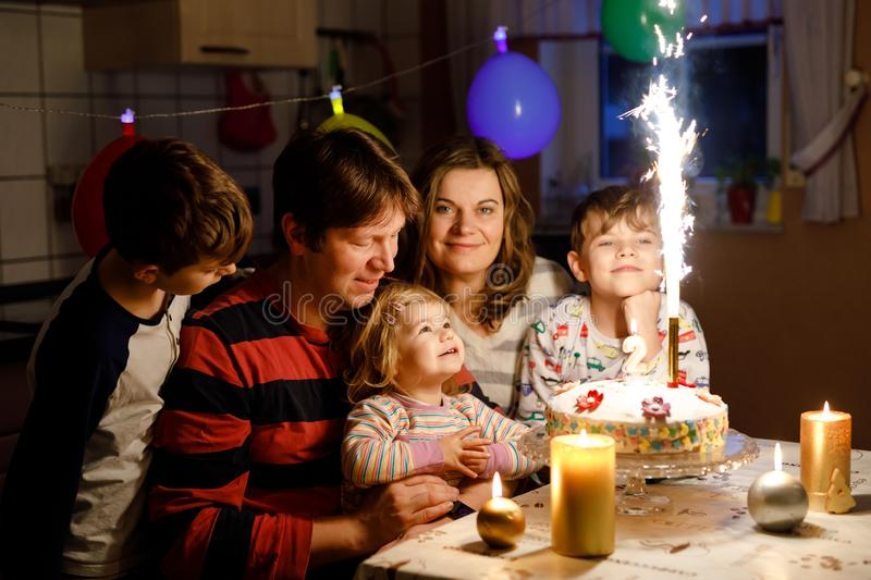Adorable little toddler girl celebrating second birthday. Baby child, two kids boys brothers, mother and father together. With cake and candles, indoor. Happy royalty free stock photography