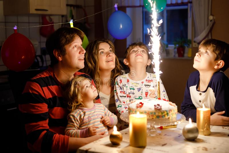 Adorable little toddler girl celebrating second birthday. Baby child, two kids boys brothers, mother and father together. With cake and candles, indoor. Happy stock photos