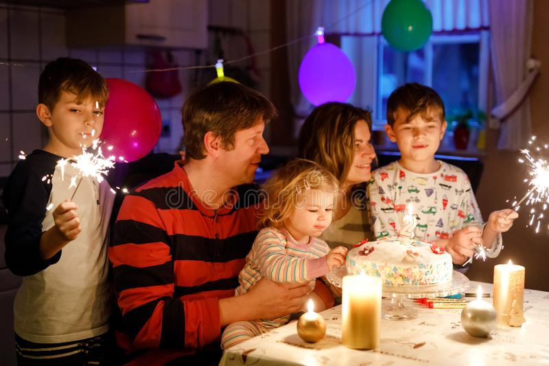 Adorable little toddler girl celebrating second birthday. Baby child, two kids boys brothers, mother and father together. With cake and candles, indoor. Happy stock image