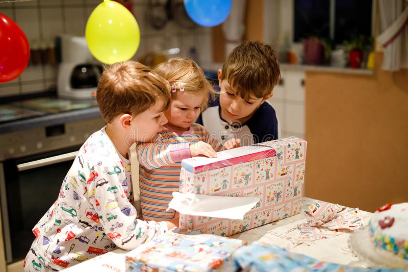 Adorable little toddler girl celebrating second birthday. Baby child and two kids boys unpacking gifts. Happy healthy. Children siblings is suprised about big stock photo
