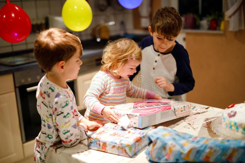 Adorable little toddler girl celebrating second birthday. Baby child and two kids boys unpacking gifts. Happy healthy. Children siblings is suprised about big royalty free stock photo