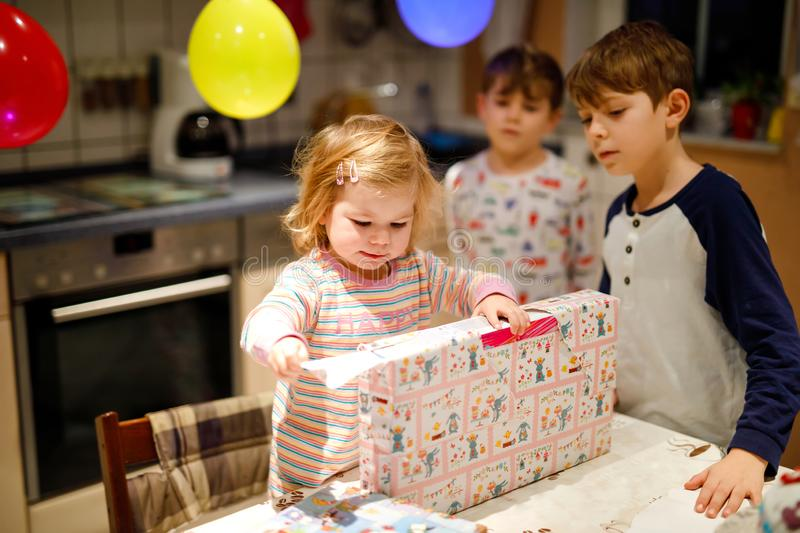 Adorable little toddler girl celebrating second birthday. Baby child and two kids boys unpacking gifts. Happy healthy. Children siblings is suprised about big royalty free stock image