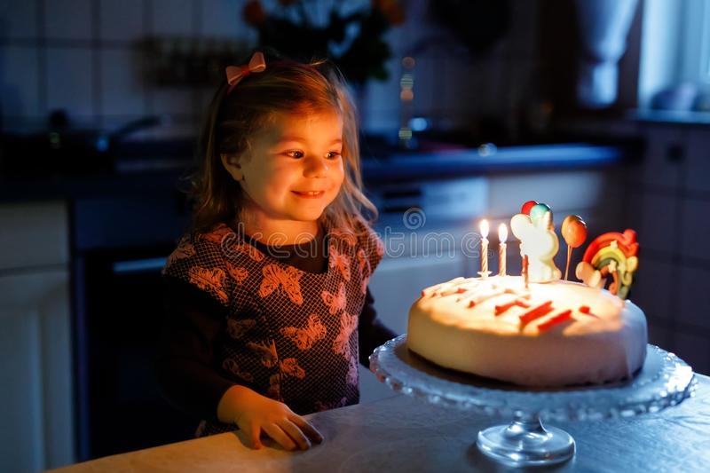 Adorable little toddler girl celebrating third birthday. Baby toddler child with homemade unicorn cake, indoor. Happy stock images