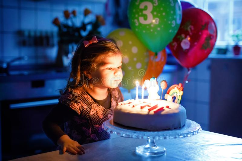 Adorable little toddler girl celebrating third birthday. Baby toddler child with homemade unicorn cake, indoor. Happy royalty free stock images