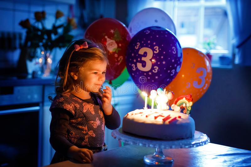 Adorable little toddler girl celebrating third birthday. Baby toddler child with homemade unicorn cake, indoor. Happy stock photography