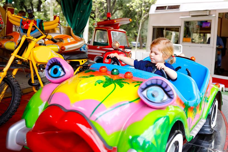 Adorable little toddler girl riding on funny car on roundabout carousel in amusement park. Happy healthy baby child royalty free stock image