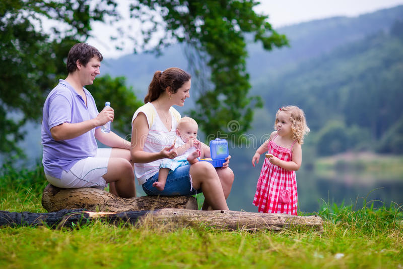 Adorable loung family with kids hiking at a lake stock image