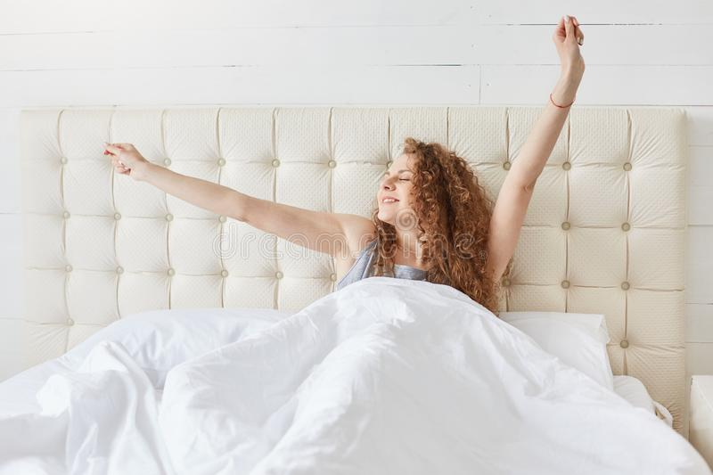 Adorable magnetic curly haired female sitting in her bed, covered by blanket, looking aside, being in high spirits, stretching, royalty free stock photo