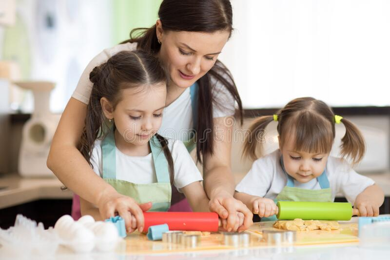 Adorable mother and daughters cooking together in the kitchen royalty free stock photos
