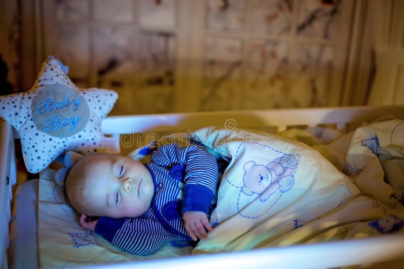 Adorable newborn baby boy, sleeping in crib at night. Little boy in blue striped pajamas taking a nap in dark room, christmas decoration in the room, winter stock photography