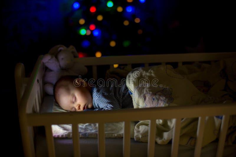 Adorable newborn baby boy, sleeping in crib at night royalty free stock photography