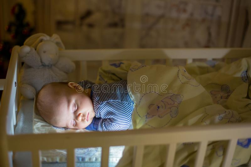 Adorable newborn baby boy, sleeping in crib at night. Little boy in blue striped pajamas taking a nap in dark room, christmas decoration in the room, winter stock images