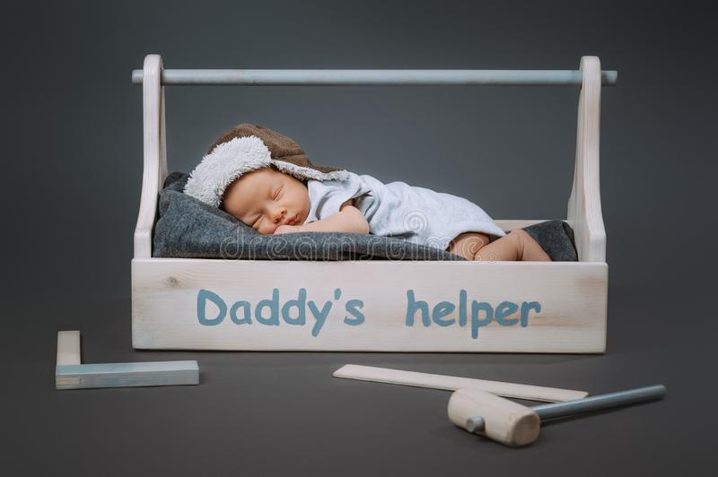 Adorable newborn baby in hat sleeping in wooden toolkit with daddys helper lettering and hammer. Near by royalty free stock photos