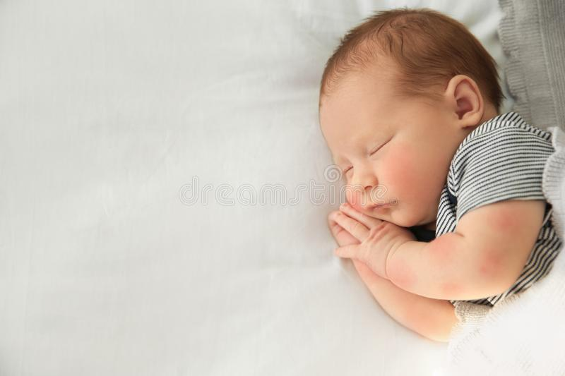 Adorable newborn baby peacefully sleeping on bed, top view. With space for text stock image