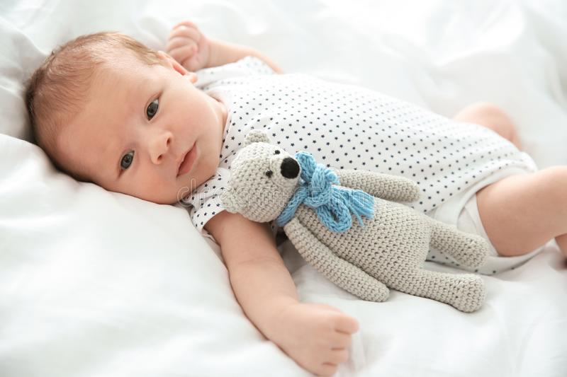 Adorable newborn baby with toy lying on bed royalty free stock image