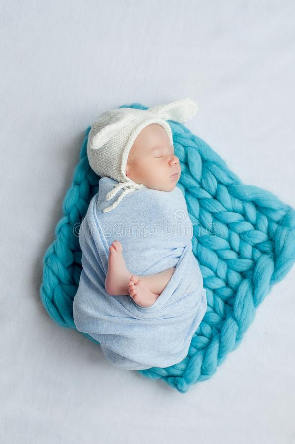 Adorable newborn child wearing bunny ears hat sleeping on a bed royalty free stock photography