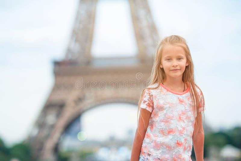Adorable niña pequeña en París al fondo de la torre Eiffel durante las vacaciones de verano foto de archivo libre de regalías