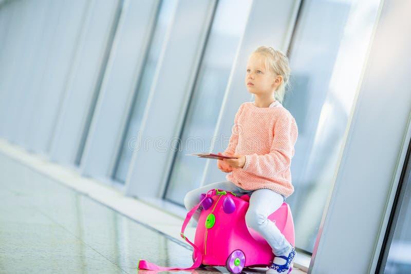 Adorable niñita en el aeropuerto con su equipaje esperando el embarque imagenes de archivo