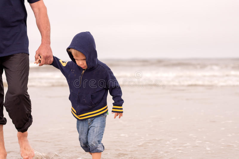Adorable obedient toddler boy walking on a beach stock images