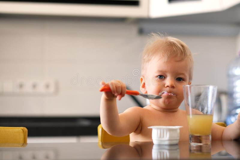 Adorable one year old baby boy eating yoghurt with spoon stock image