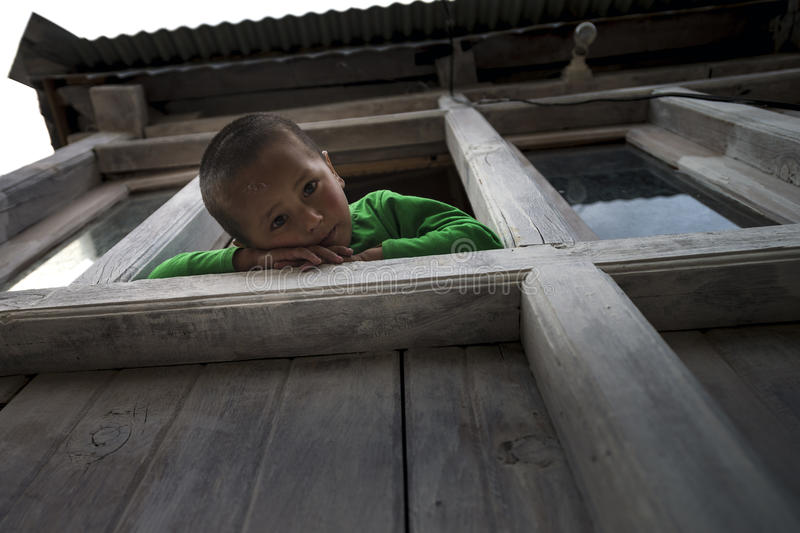 Adorable and playful young boy climb and sit at window ledge of home, looking down and leg stuck out. Low angle view of asian active boy siting at window ledge royalty free stock image