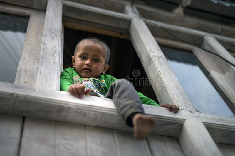 Adorable and playful young boy climb and sit at window ledge of home, looking down and leg stuck out. Low angle view of asian active boy siting at window ledge royalty free stock photos