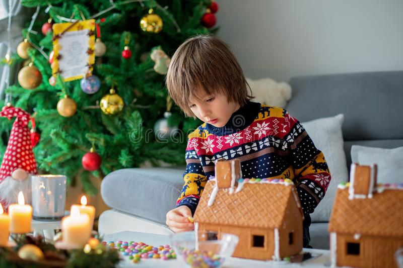 Adorable preschool children, boy brothers, decorating gingerbread houses. Adorable preschool child, boy, decorating gingerbread houses for Christmas at home royalty free stock photography
