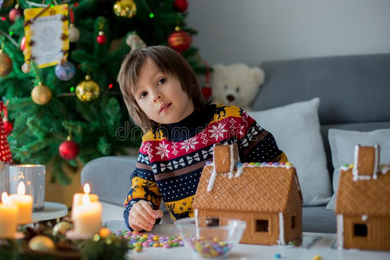 Adorable preschool children, boy brothers, decorating gingerbread houses. Adorable preschool child, boy, decorating gingerbread houses for Christmas at home stock photo