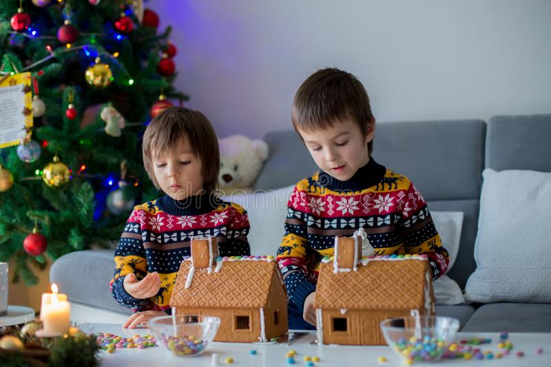 Adorable preschool children, boy brothers, decorating gingerbread houses. For Christmas at home, christmas tree behind them, advent candles on the table stock image