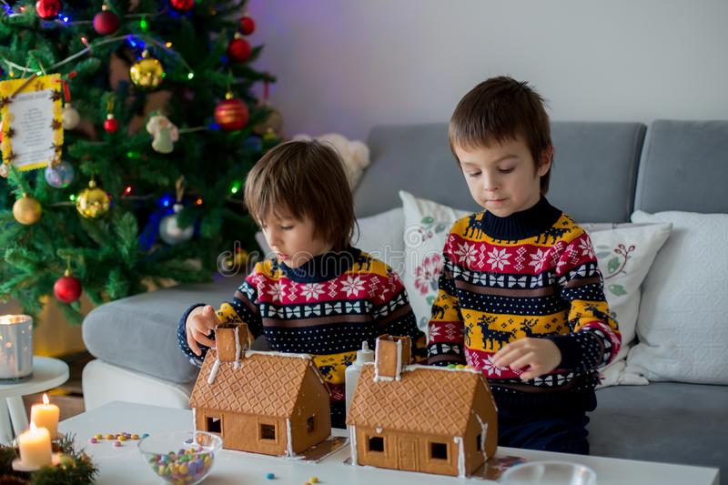 Adorable preschool children, boy brothers, decorating gingerbread houses. For Christmas at home, christmas tree behind them, advent candles on the table stock photography