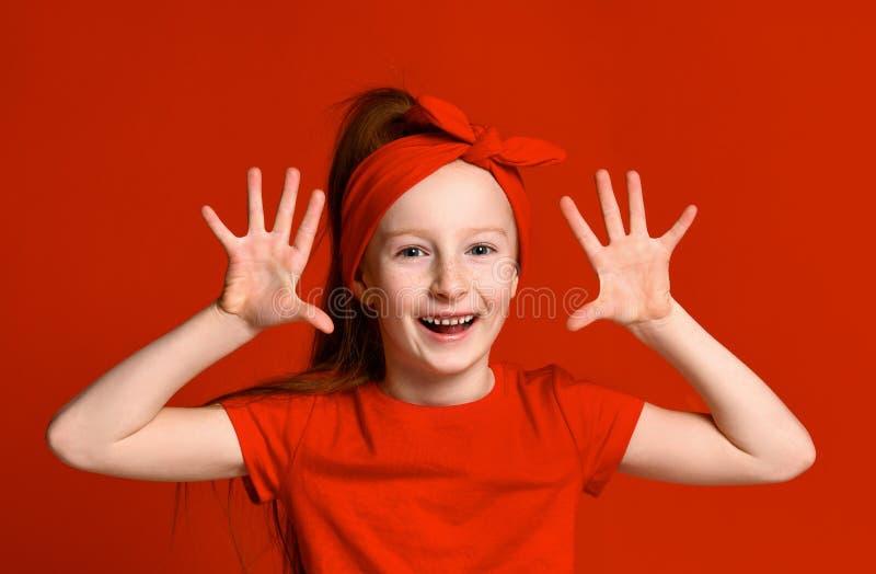 Adorable preschooler girl showing palms and funny grimace. Cute joyful Hispanic child having fun. Fun concept stock photo