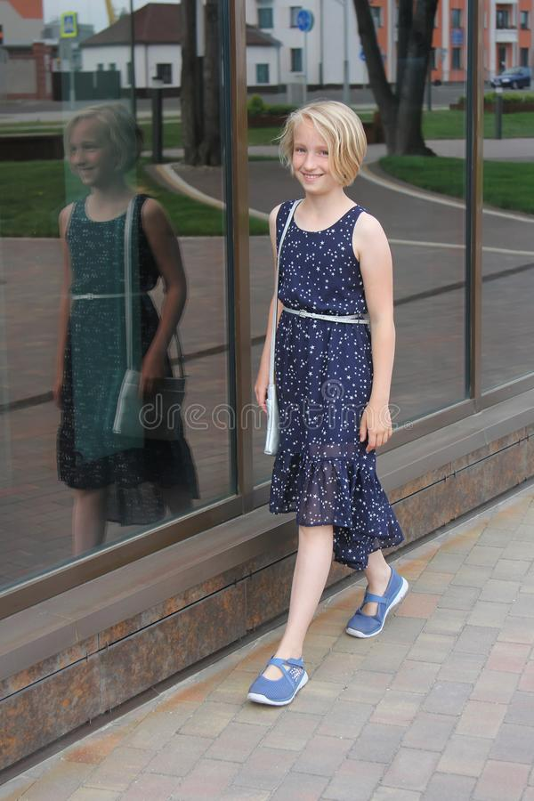 Adorable preteen blonde kid girl in fashionable dress walking down the street, she smiles and is confident royalty free stock photos