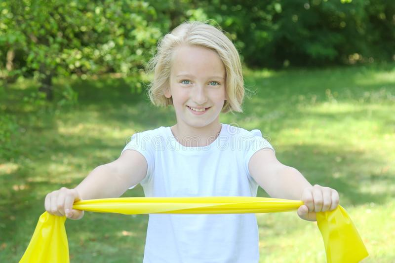 Adorable preteen blonde kid girl playing sports with a rubber band outdoors in the park. Healthy lifestyle royalty free stock photo