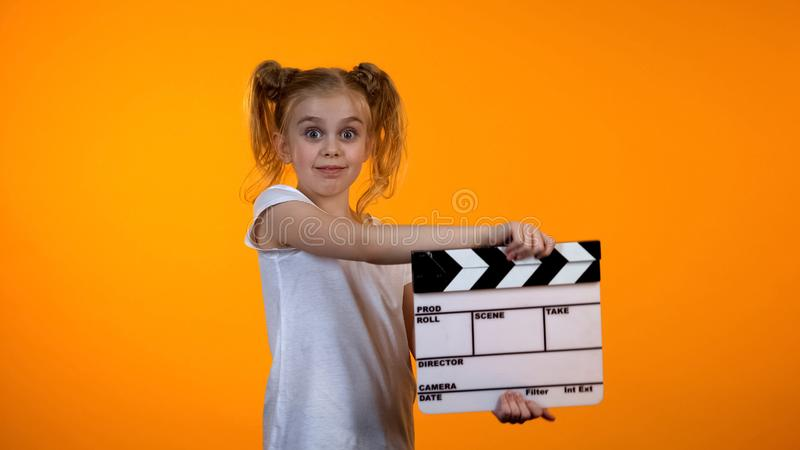 Adorable preteen girl clapping flapper pretending to be film producer, dream royalty free stock images