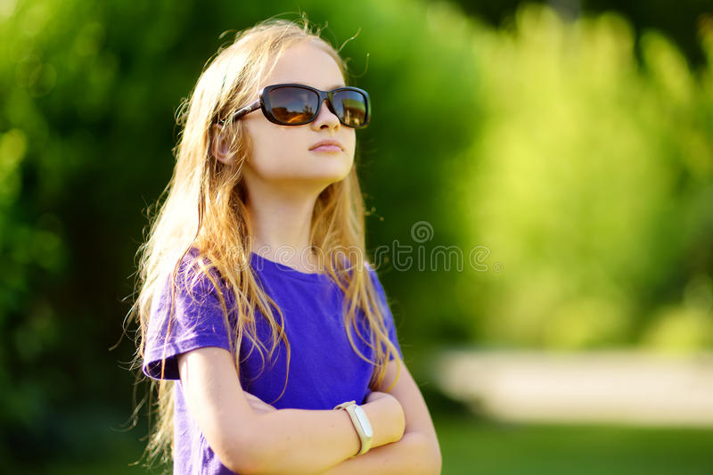 Adorable preteen girl wearing sunglasses on sunny summer day stock image