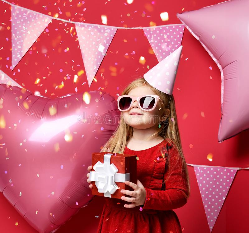 Adorable pretty girl with pink balloons and red present gift and birthday cap. Three years girl toddler kid with pink balloons and flags hold red present gift royalty free stock photography