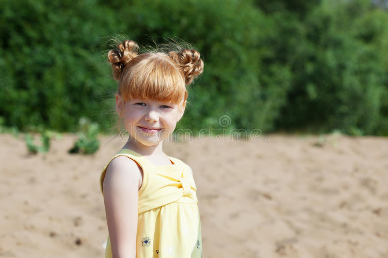 Adorable red-haired girl posing at camera in park. Close-up stock images