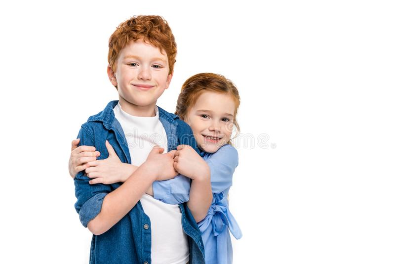 adorable redhead siblings hugging and smiling at camera stock photo