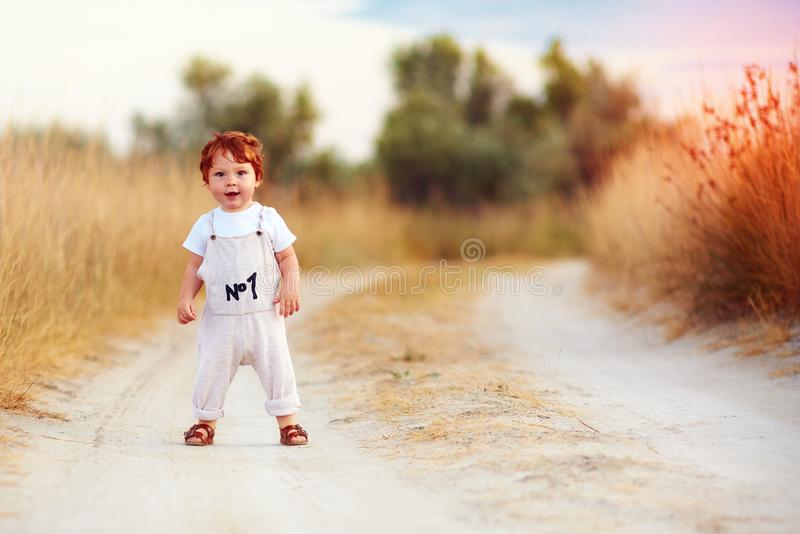 Adorable redhead toddler baby boy in jumpsuit walking along rural summer road in sunburnt field royalty free stock images
