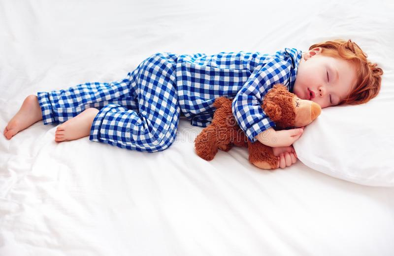 Adorable redhead toddler baby in flannel pajamas sleeping with plush warmer toy royalty free stock photo