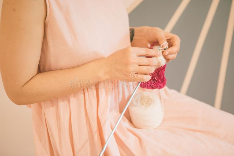 Adorable relaxed knitting hobby. Woman in pink dress. stock images