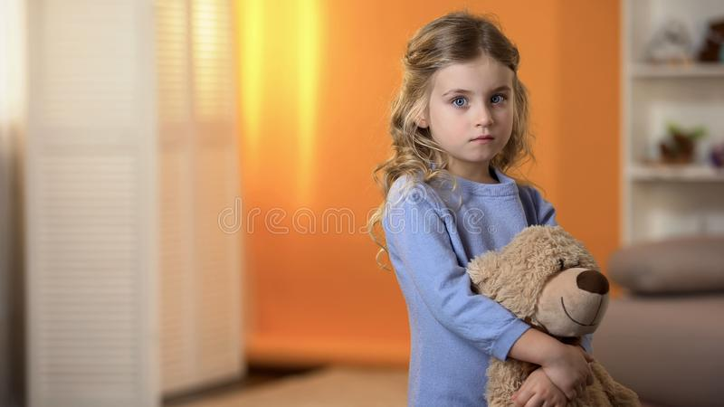 Adorable sad little girl hugging favorite teddy bear feeling lonely in orphanage royalty free stock photography