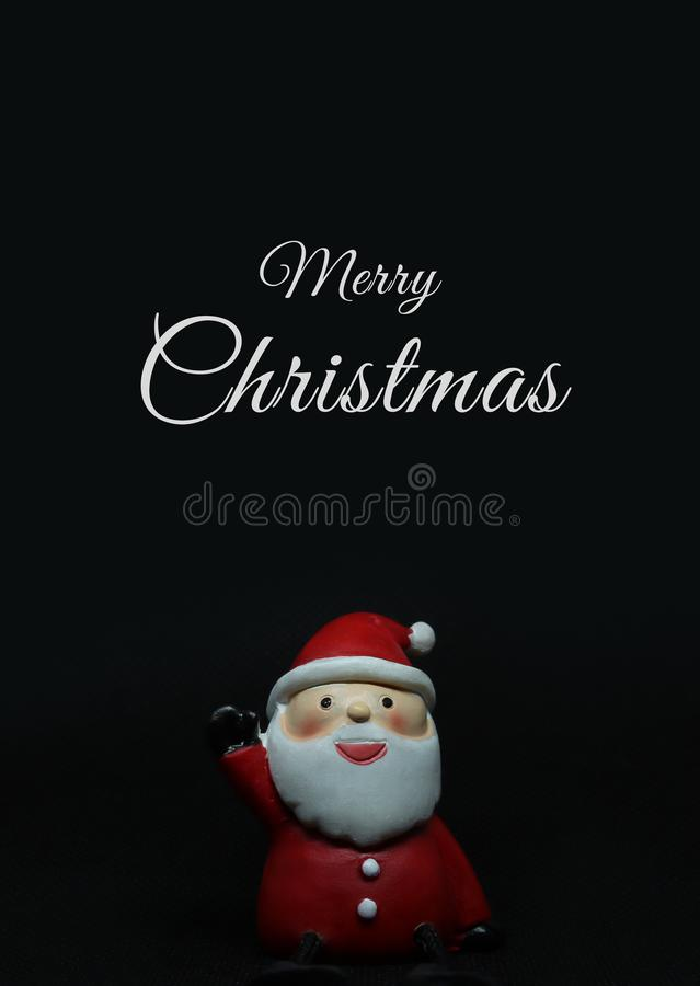 Adorable santa claus doll on black background with white Merry Christmas text above. Vertical photo of an adorable santa claus doll on black background with stock images