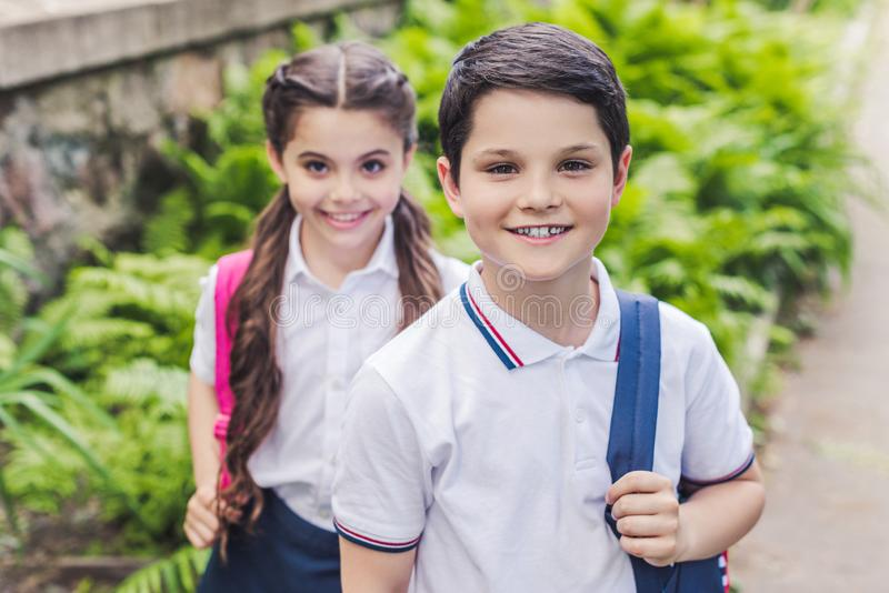 Adorable schoolchildren with backpacks looking at camera. In park royalty free stock photo