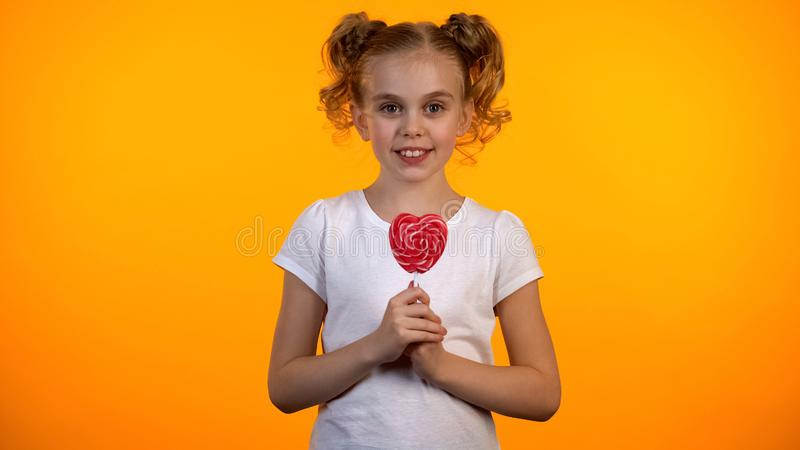 Adorable schoolgirl holding heart-shaped lollipop, happy child, confectionery royalty free stock photography
