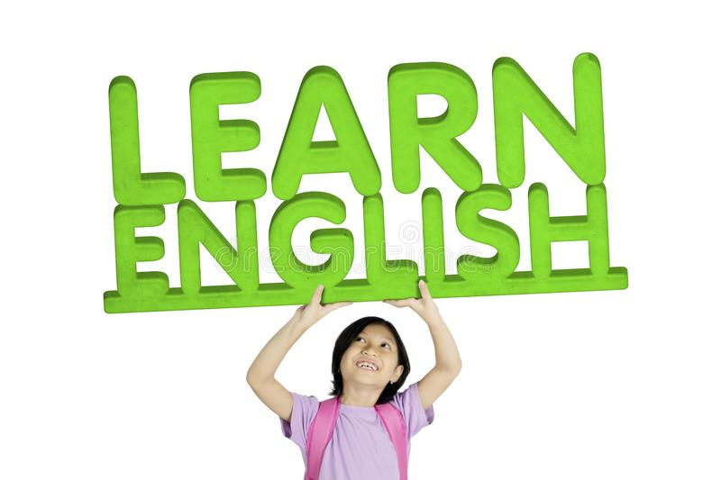 Adorable schoolgirl lifting word of Learn English royalty free stock photos