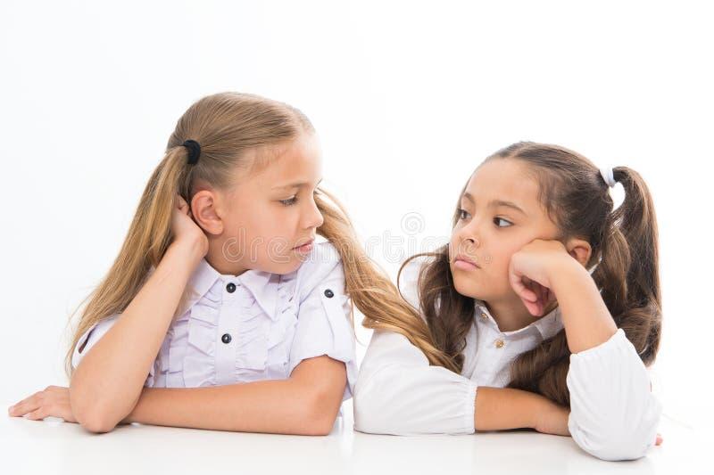 Adorable schoolgirls. Formal style. Happy childhood. Schoolgirls sit at desk white background. Schoolgirls emotional stock photo
