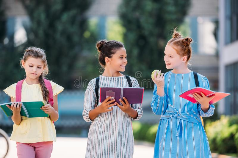 adorable schoolgirls with notebooks spending time together after royalty free stock image